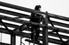 O construtor trabalha no sunsetblack e na foto branca de um soldador mascarado que trabalha na altura foto de stock