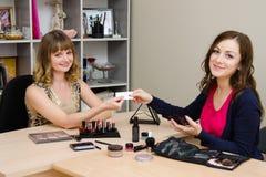 O consultante de beleza envia ao cliente um cartão Foto de Stock Royalty Free