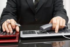 O consultante está trabalhando no computador e está chamando o cliente Fotografia de Stock Royalty Free