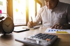 O contador calcula a finança do lucro anual pelo calculato da imprensa imagens de stock royalty free