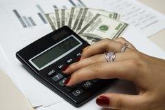 O contador conta o dinheiro com uma calculadora Imagens de Stock Royalty Free