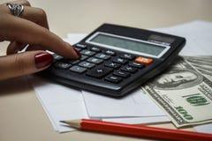 O contador conta o dinheiro com uma calculadora Imagem de Stock