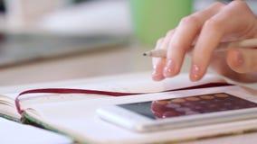 O contador fêmea calcula números O guarda-livros calcula no telefone esperto video estoque