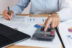 o contador que usa a calculadora com a pena na mesa para calcula finan imagem de stock