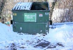 O contentor do lixo dos irmãos do inverno senta vazio em um parque de estacionamento snowplowed imagens de stock