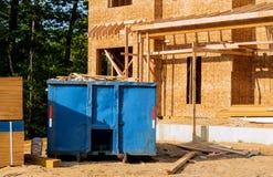 O contentor, recicla escaninhos do desperd?cio e de lixo perto do canteiro de obras novas da constru??o de casas do apartamento fotografia de stock