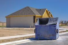 O contentor senta-se fora da casa da construção nova imagens de stock