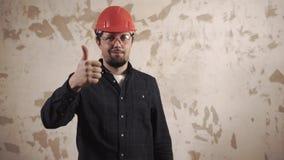 O contramestre com o chapéu protetor vermelho em uma cabeça está estando dentro e polegar acima video estoque
