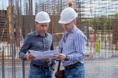 O contramestre e o contratante estão olhando o projeto no canteiro de obras Fotografia de Stock Royalty Free