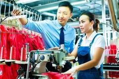 O contramestre em uma fábrica explica algo fotografia de stock