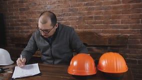O contramestre masculino que senta-se atrás de uma mesa no escritório no local e volta a calcular o capacete video estoque