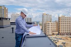 O contramestre no capacete branco e os óculos de sol no telhado estão olhando o projeto Foto de Stock