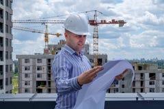 O contramestre no capacete branco no telhado está olhando o projec Imagem de Stock Royalty Free