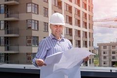 O contramestre ou o inspetor no capacete branco estão olhando o projeto Foto de Stock Royalty Free