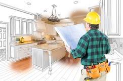 O contratante masculino com capacete de segurança e planos olha a cozinha feita sob encomenda foto de stock
