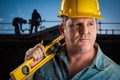 O contratante sério com capacete de segurança e nível olha sobre no Worksite Imagens de Stock