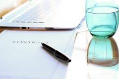 O contrato do negócio com pena está pronto para assinar Um vidro da água Imagens de Stock Royalty Free