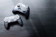 O controlador de Xbox e de Playstation sentou-se pr?ximos um do outro em um fundo escuro foto de stock