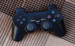 O controlador do jogo de vídeo do console do jogo está no sofá quadriculado Dispositivo sem fios para controlar durante o jogo de fotos de stock