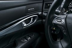 O controle dos meios abotoa-se no volante no interior de couro perfurado preto com monitor do computador Detalhe moderno do inter imagens de stock