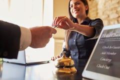 O convidado pega a sala o cartão chave na mesa de registro do hotel, fim Imagens de Stock Royalty Free