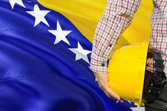 O coordenador bosniano está guardando o capacete de segurança amarelo com ondulação do fundo da bandeira de Bósnia - de Herzegovi fotos de stock royalty free