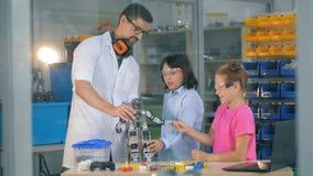O coordenador com crianças da escola estuda tecnologias robóticos inovativas no clube da ciência