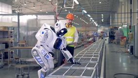 O coordenador da fábrica controla um robô, quando trabalhar com uma ferramenta 4K vídeos de arquivo