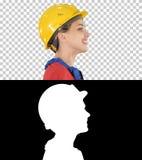 O coordenador da jovem mulher com o capacete de segurança amarelo que anda e que sorri, Alpha Channel imagens de stock royalty free
