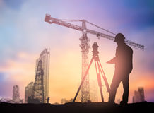 O coordenador da silhueta que olham carregadores e os caminhões em uma construção sentam-se Fotos de Stock Royalty Free
