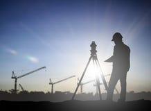 O coordenador da silhueta que olham carregadores e os caminhões em uma construção sentam-se Fotografia de Stock Royalty Free