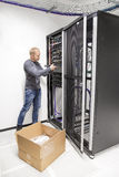 O coordenador da TI instala o interruptor de rede no datacenter Imagens de Stock Royalty Free