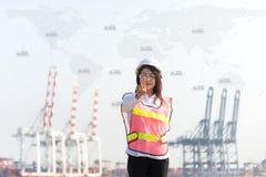 O coordenador das mulheres que trabalha com o navio do frete da carga do recipiente no estaleiro no crepúsculo para o fundo logís Imagem de Stock