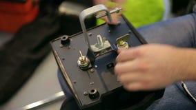 O coordenador do homem repara o equipamento de iluminação na fase video estoque