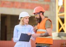 O coordenador e o construtor da mulher comunicam o canteiro de obras Discuta o plano do progresso Relacionamentos entre a constru imagem de stock