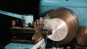 O coordenador em um torno trabalha com um bloco de alumínio, microplaquetas do metal voa no movimento lento vídeos de arquivo