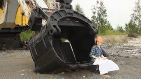 O coordenador fêmea examina um esquema que senta-se em uma grande cubeta de uma máquina escavadora vídeos de arquivo