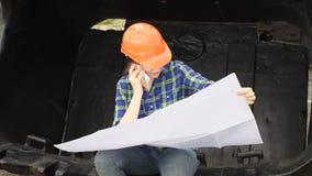 O coordenador fêmea examina um esquema que senta-se em uma grande cubeta de uma máquina escavadora filme