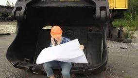 O coordenador fêmea examina um esquema que senta-se em uma grande cubeta de uma máquina escavadora video estoque