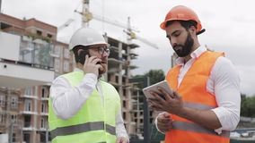 O coordenador fala no telefone celular no canteiro de obras e verifica o trabalho do trabalhador Negocia??es do construtor no sma vídeos de arquivo