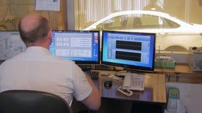 O coordenador idoso está olhando dados nas exposições de computadores industriais em uma fábrica do carro, examinando video estoque