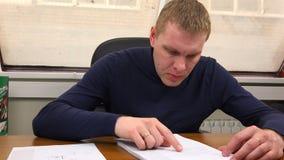O coordenador lê desenhos e limpa o suor da testa com a mão filme