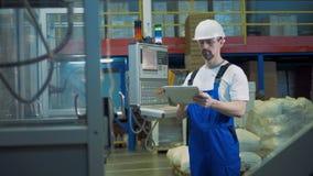 O coordenador masculino com uma tabuleta está inspecionando o processo industrial da fabricação video estoque