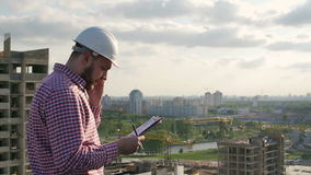 O coordenador masculino discute o projeto no telefone video estoque
