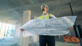 O coordenador masculino está estando no meio de um canteiro de obras com o modelo em suas mãos video estoque