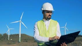 O coordenador masculino trabalha fora, olhando turbinas eólicas e datilografando em um portátil vídeos de arquivo