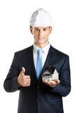 O coordenador mostra a casa e os polegares modelo acima Foto de Stock