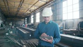 O coordenador na fabricação com uma tabuleta video estoque