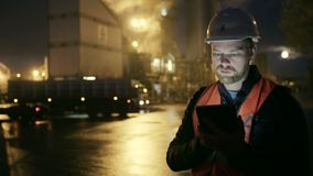 O coordenador no capacete de segurança com um tablet pc olha o caminhão na fábrica da indústria pesada vídeos de arquivo