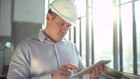 O coordenador no capacete de segurança está guardando um tablet pc em uma fábrica da indústria pesada Lento-movimento video estoque